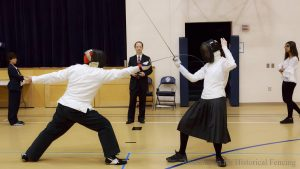 Director Kim Moser officiating foil fencing bout